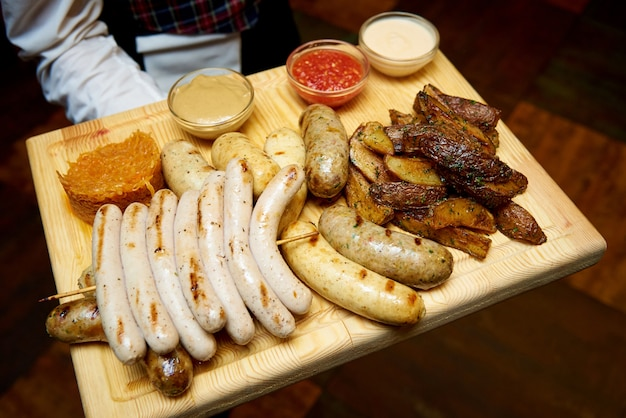 Appetizer for beer from sausages and potatoes with different sauces on a board in the hands of a waiter