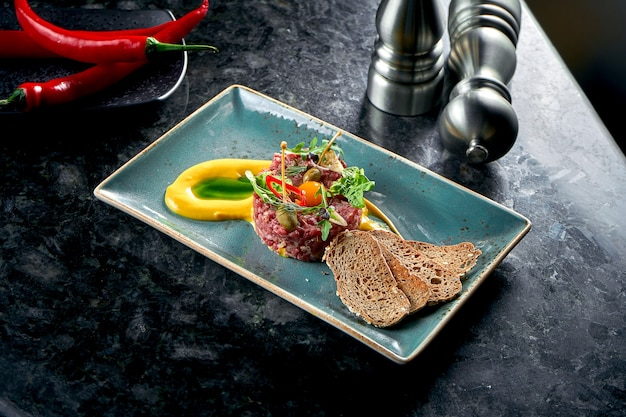 An appetizer before the main course - beef steak tartare served with croutons, cappers, yolk, pickles in a blue plate on a marble table. restaurant food. raw meat