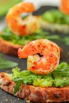 Appetizer of bread with  seeds, shrimp, avocado and arugula.
