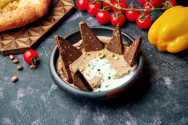 Закуска куриный паштет с белым соусом и орехами с ржаным хлебом в черной миске.