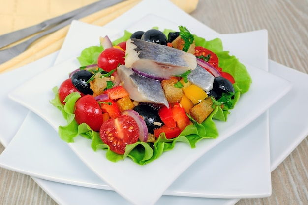 Appetizer of fresh vegetables with crackers and herring