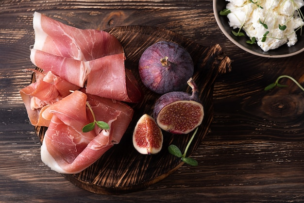 Appetizer from dry cured ham, prosciutto slices with figs on a dark wooden background, rustic style.