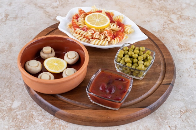 Ингредиенты для закуски с тарелкой макарон на мраморной поверхности.