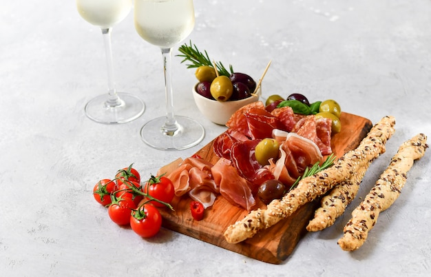Appetizer in italian restaurant with prosciutto and salami, olives  and two glasses prosecco