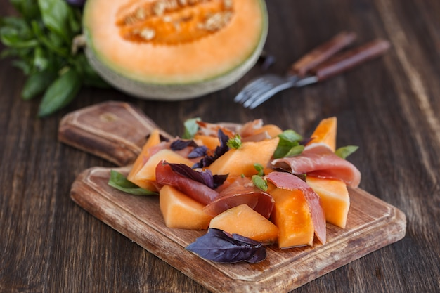 Appetizer, melon with jamon and basil. summer salad for a party