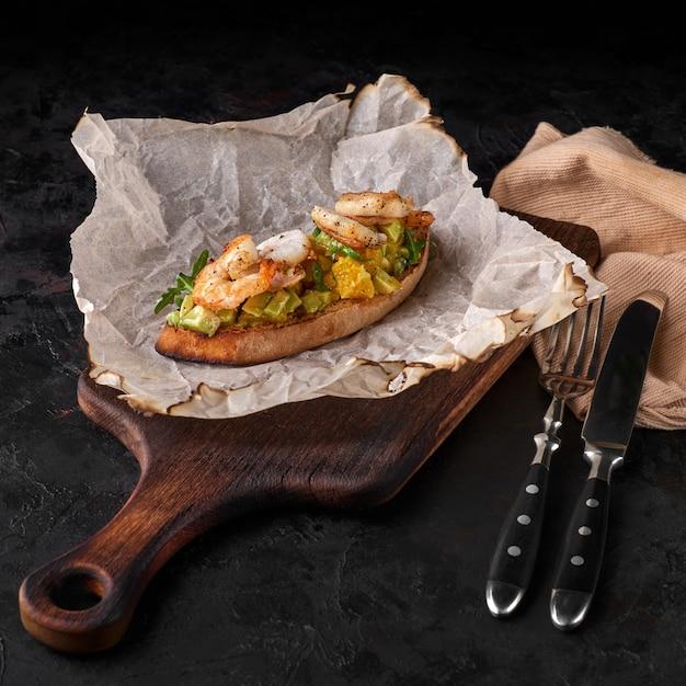 エビ、アボカド、柑橘系のブルスケッタを添えたパンの前菜。クロスティーニ。ブルスケッタ。