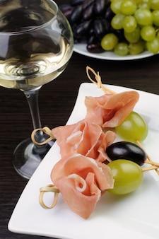 白ワインとグラスで串に刺したハムとブドウの前菜