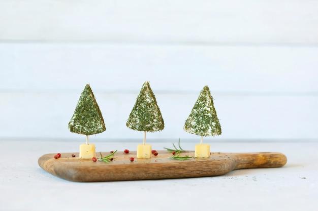 Закуска новогодних елок из сыра и украшенная укропом, легкое приготовление, на деревянной разделочной доске, вид сбоку