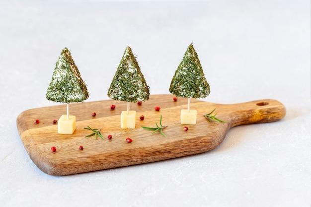 木製のまな板の側面図にディルで飾られたチーズの新年の木の前菜