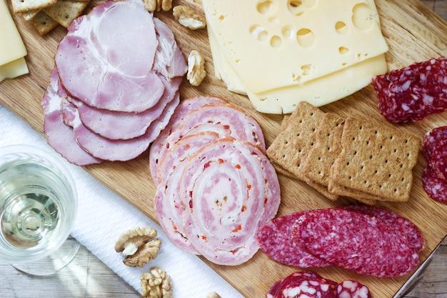 Закуска из различных видов колбас, мяса, сыров и крекеров на деревянной доске, подается к вину.