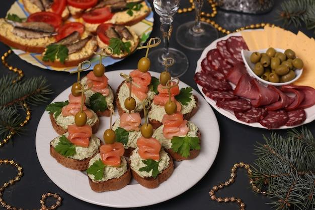 Закуска на праздничный стол - канапе с лососем, бутерброды со шпротами и нарезанным сыром и колбасой.