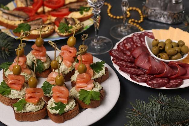 お祝いテーブルの前菜-サーモンのカナッペ、スプラットとスライスチーズとソーセージのサンドイッチ
