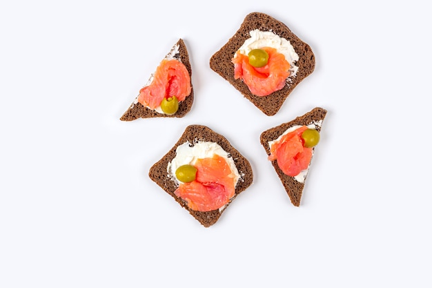 Appetizer, open sandwich with salmon and soft cheese on white background. traditional italian or scandinavian cuisine.