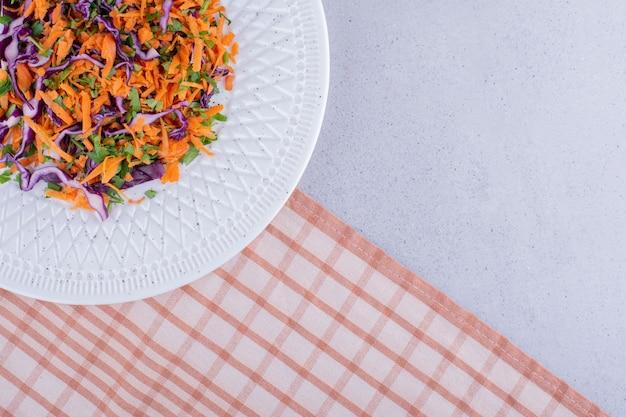 대리석 배경에 양배추와 당근 샐러드의 전채 부분. 고품질 사진