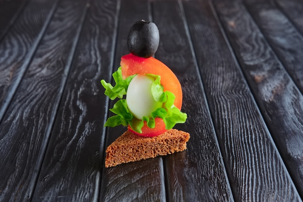 Appetizer for reception. brown bread with quail egg, tomato, salad leaf and olive on skewer