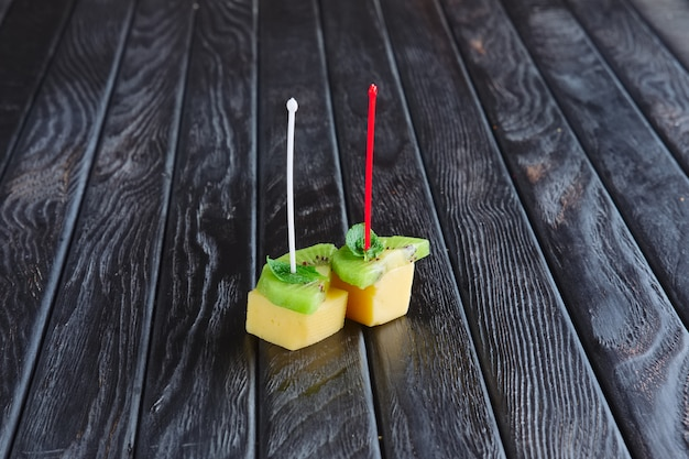 Appetizer for reception. cheese, kiwi and leaf of mint on skewer