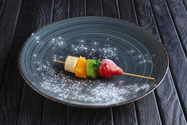 Appetizer for reception. fresh banana, orange, kiwi, strawberry on skewer