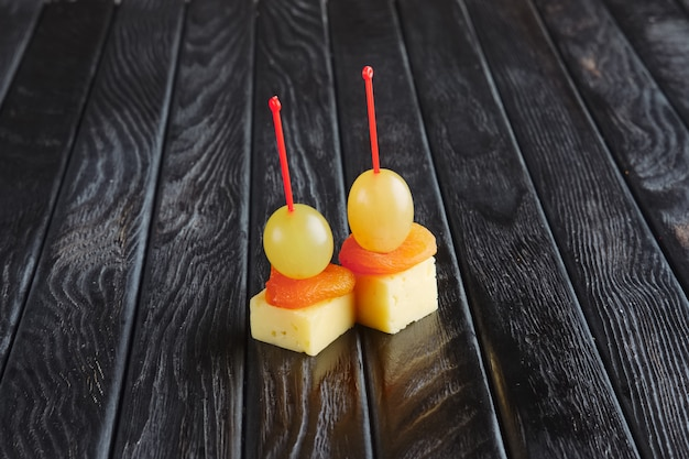 Appetizer for reception.  ãâ¡heese, dried apricot and grape on skewer