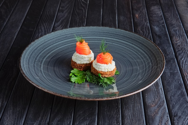 Appetizer for reception. smoked salmon with ricotta and dill on piece of brown bread