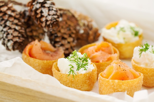 Appetizer salmon with fresh cheese on board