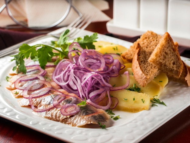 Appetizer of salted herring, red onion, potatoes and rye bread