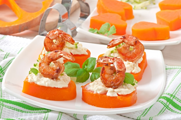 Appetizer of shrimp and cream cheese on pumpkin hearts