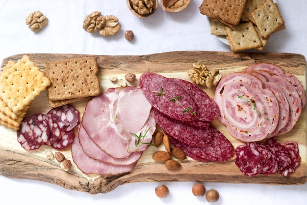 Appetizer of various types of sausages, meats, cheeses and crackers on a wooden board, served to wine.
