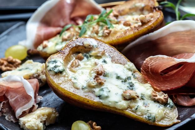 Закуска из груши, запеченной с голубым сыром, орехами и медом, прошутто. предпосылка рецепта еды. закройте вверх.