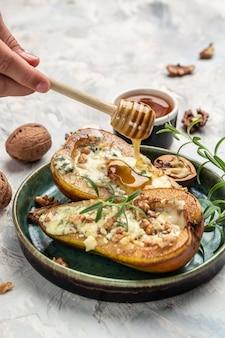 Закуска с грушей, запеченной с голубым сыром, орехами, полив медом. французская кухня. кето диета. вкусный завтрак или закуска, чистое питание, диета, концепция веганского питания. вид сверху,