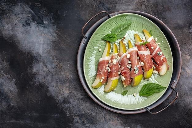 Закуска с грушей, голубым сыром и ветчиной прошутто, здоровые жиры, чистая еда для похудания, длинный баннерный формат. вид сверху
