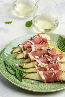 Закуска с грушей, голубым сыром, ветчиной прошутто и базиликом. итальянские закуски с белым вином, вид сверху.