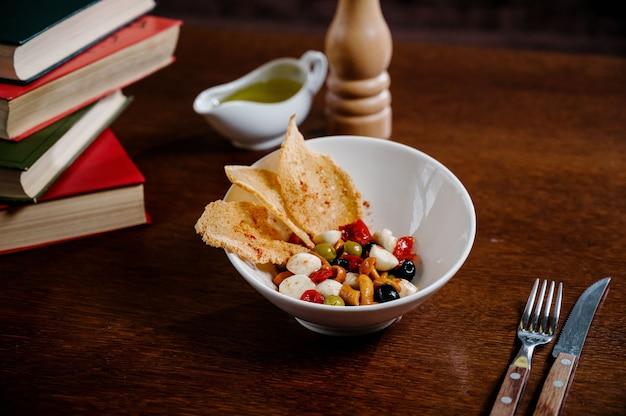 キノコのピクルス、オリーブ、パルメザンチーズを木の表面に添えた前菜