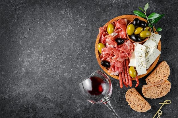 어두운 콘크리트 배경에 고기, 치즈, 올리브가 있는 전채 나무 접시. 복사 공간, 평평한 위치.
