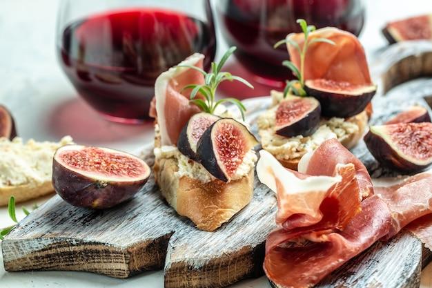 전채. 전채, 스낵 및 와인. 프로슈토, 크림 치즈, 무화과가 있는 샌드위치, 위쪽 전망.