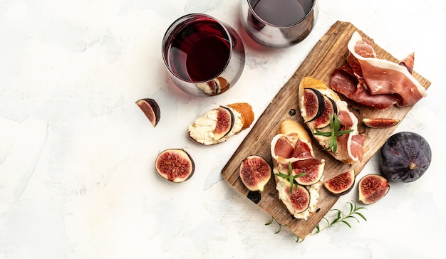 Appetizers. antipasti, snacks and wine. sandwich with prosciutto, cream cheese and figs. banner, menu, recipe place for text, top view.