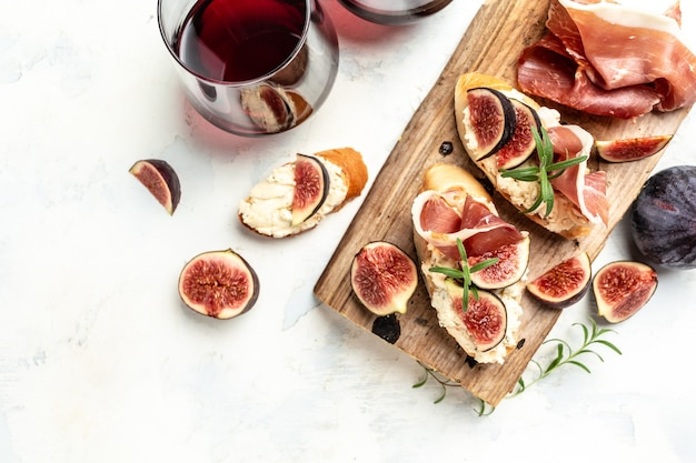Appetizers board with traditional spanish tapas set. italian antipasti bruschetta with prosciutto, cream cheese and figs for wine. banner, menu, recipe place for text, top view