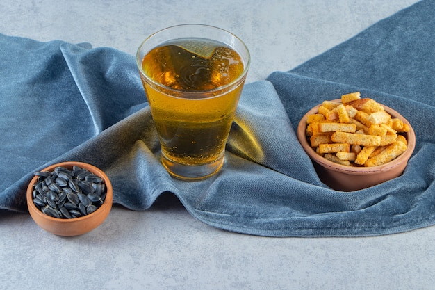 Appetizers in a bowls next to a glass of beer on pieces of fabric, on the blue surface.