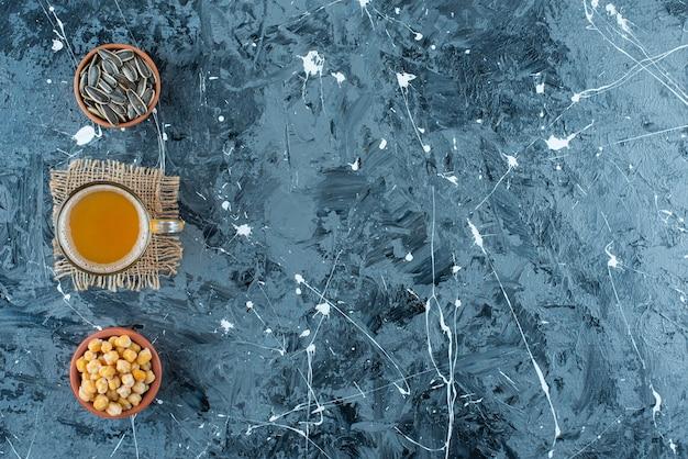 Antipasti in ciotole accanto a un bicchiere di birra sulla trama, sul tavolo blu.