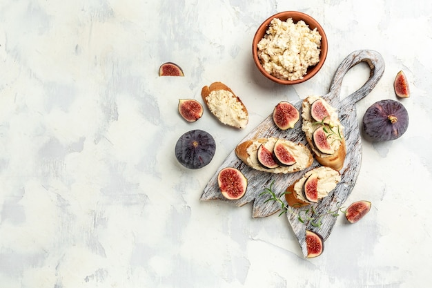 Закуски. брускетты с инжиром, мягким сыром. вкусный завтрак или закуска, чистое питание, диета, концепция веганского питания. вид сверху.