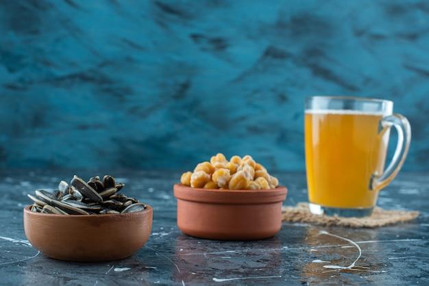 Закуски в мисках рядом с бокалом пива на текстуре, на синем фоне.