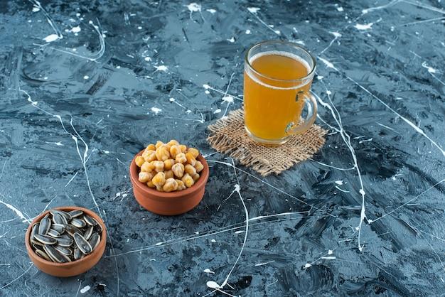 青いテーブルの上で、テクスチャーのビールのグラスの横にあるボウルの前菜。