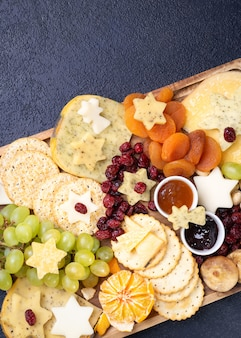 Appetizers platter with various types of cheese, grapes, dried figs, cranberries, pistachios and jams