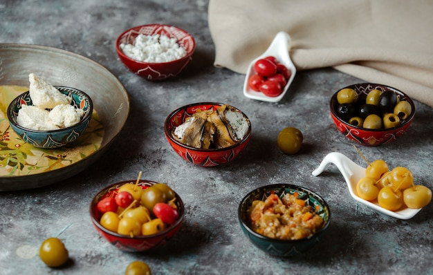 Appetizers in small sauce bowls containing marinated foods, olives and cream cheese