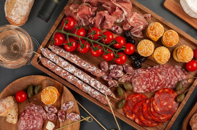 Appetizers table with diferents antipasti, cheese, charcuterie, snacks and wine. mini burgers, sausage, ham, tapas, olives, cheese and baguette over grey concrete surface. top view, flat lay