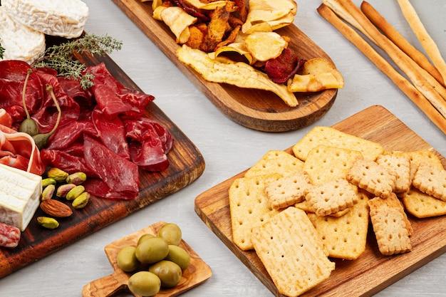 Стол закусок с различными закусками, колбасными изделиями, закусками и вином. колбаса, ветчина, тапас, оливки, сыр и крекеры для фуршета. вид сверху, плоская планировка