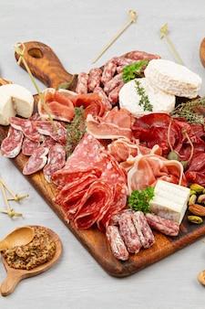 Таблица закусок с различными закусками, мясными закусками, закусками и вином