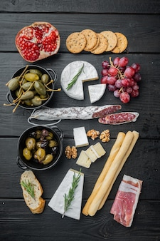 Appetizers table with differents antipasti set, on black wooden table, flat lay