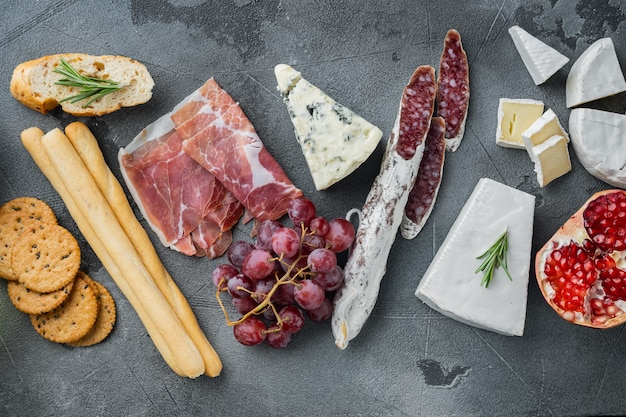 Appetizers table with differents antipasti set, on gray background, flat lay
