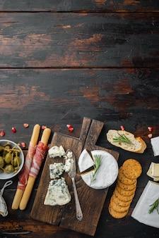Таблица закусок с различными наборами закусок, на темном деревянном фоне, вид сверху с местом для текста