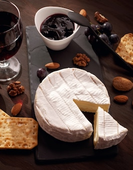 Стол закусок с французским сыром камамбер и виноградом для фуршета аперитив